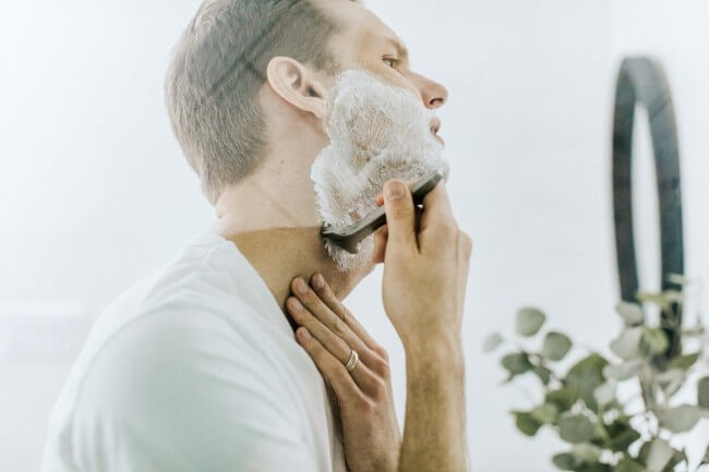 a man shaving beard in front of mirror in bathroom
