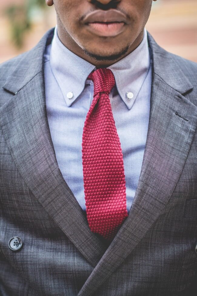 man in suit with a red knitted tie