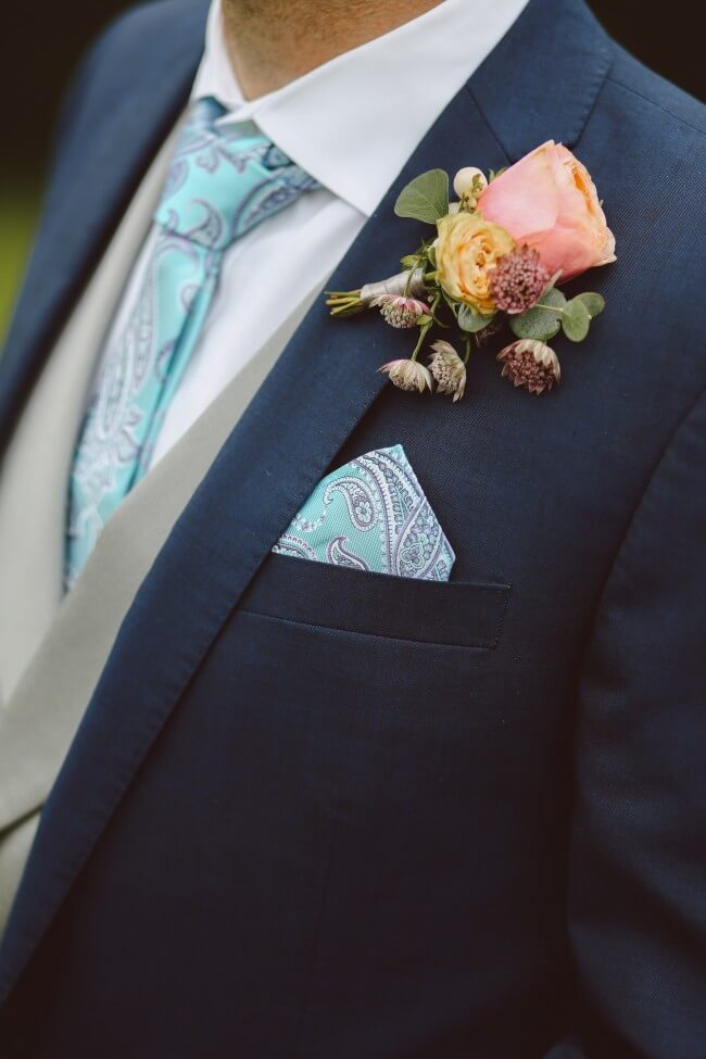 man in suit with pastel paisley tie