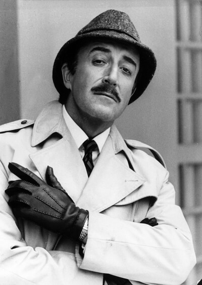 Peter Sellers as Inspector Clouseau in his legendary outfit of trench coat and trilby tweed hat.