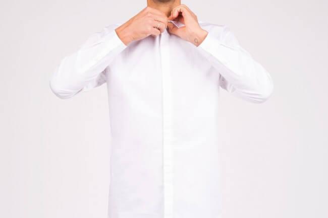 man buttoning up shirt